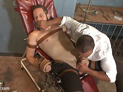 Wolf Hudson has found a new job but in order to start work he needs a physical, so he finds the only place his HMO will cover, Dr. Micah Brandt's office.  The creepy doctor tricks Wolf into medical restraints and has his way with his patient's big uncut dick.  Once Micah turns his back to grab more