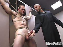Jonah Marx is cruising the bathroom and notices someone in the stall next to him.  Eager to blow his load, Jonah offers his cock to his neighbor but just before he blows his load he's taken down and hoisted up by his wrists.  Blindfolded with a gag in mouth, Jonah's clothes are torn away as the pervy handyman has his way.  Against his will, Jonah's brought to the edge of orgasm over and over before he's denied any pleasure.  Bent over in the stalls he's fucked from behind with a machine before receiving a foot job.  A cascade of cum shoots from Jonah's aching cock before he's tormented with a severe apple polishing to drive him wild.