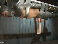 Straight stud Zane Anders finds himself belted down to a ladder, balanced against the wall of a dark workshop. His captors emerge from the shadows and cut the clothes from his body, running their hands over every inch of it. Fear gets overtaken by sheer horniness for Zane, as his captors edge his cock repeatedly. They move Zane to a suspended platform and mummify him in duct tape while continuing to deny an orgasm for Zane's throbbing dick. Leaving his feet exposed, his captors make the stud squirm in his casing as they suck and lick his toes. They flip Zane's platform and milks his dick from below as he swings over the ground. Zane returns upright and finally has permission to cum, blowing a massive load that soon gets smeared all over his face. His captors give his dick a hard apple polish and completely encase him in duct tape.