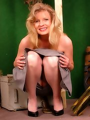Platinum-blonde military girl in grey colored stockings and long dress