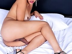 Busty transsexual Thaina posing on the bed