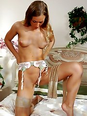 Luring babe strokes her pussy with her hand clad in her striped stockings