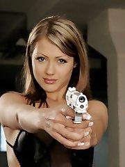 A brunette hottie posing with a gun.