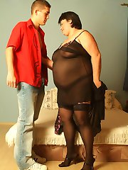Sexy fat mature model stripping off in front of a younger guy to lure him into lending her his dick
