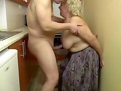 Naughty, blonde granny is playing with her tits and her lovers dick, in the kitchen