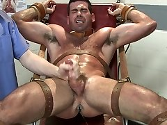 Muscled stud strapped down and has his cock milked at the sperm bank