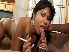 Asian babe with lovely tits smokes cigarette and gets spunk facial on couch