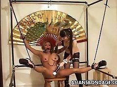 Restrained Asian chick tormented by her smoking hot dominatrix