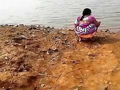 Indian woman urinating in the dirt by a lake
