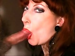 mature redhead wearing red lipstick and blowing cock