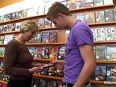 Sexy platinum-blonde mature fucks him in the video store