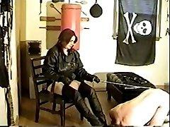 Mature dominatrix in latex boots