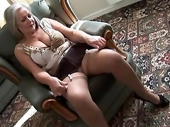 Attractive big-boobed granny in stockings disrobing