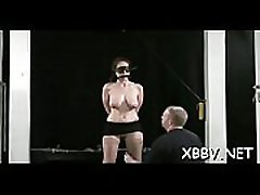 Bare wife stands tied up and endures heavy breast bondage