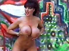 Huge boobed brunette poses nude