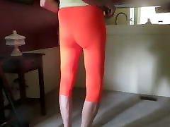 Male slut in skin-tight, bright orange spandex leggings.