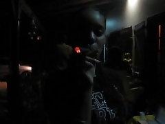 Young cute black girl smokes a cigar