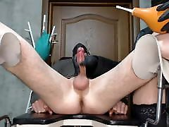 Mistress in a leather jacket gives the patient an enema