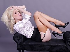 Gorgeous leggy blonde Emma flashes her stockings and suspender belt in tall black high heels