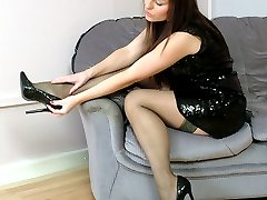 Gorgeous Sara is ready for a night out in a shiny black dress, silky stockings and matching high...
