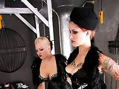 Two sexy femdoms use a humbler and clothespins on their slave's cock and balls.