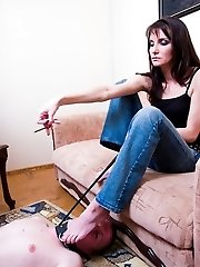 Lying at her feet, the guy serves his lady for a carpet, a foot licker and an ashtray