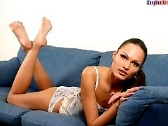 Slim goddess shows her feet and tits lying on a sofa