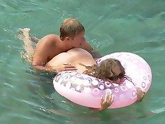 Naked lovers slyly filmed having sex fun in the sea