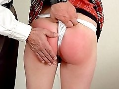 Chubby redhead bending over the table for some hand caning