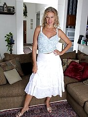Busty blonde housewife Cally Jo fingers her pussy on the sofa.