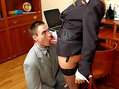 Lascivious lady boss armed with strap-on showing guy how to work with tool