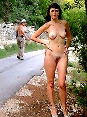 Female nudist posing on a road