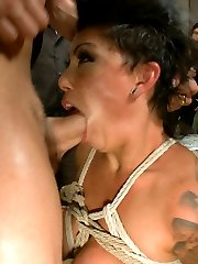 Curvy reality tv star Cameron Bay loves attention, but she has no idea what she's in for when she signs up for Public Disgrace. Lorelei ties up her D-cup tits and drags her into a dirty Mission punk club where Cameron immediately has her clothes ripped off by the rough crowd.  She asked for humiliation and rough sex, and she gets both as she's spanked and tit-slapped and called names by strangers, bent over a table and fucked in the ass, and told to suck the cock of a strange man who unzips his pants and shoves his dick in her face.  But the biggest humiliation for this attention-whore comes when Cameron is made to stand alone on stage and foolishly attempt to masturbate with her bound hands.  When she can't make herself cum, a team of dykes pins her down and Lorelei fist-fucks her.  When she is utterly destroyed and covered in cum, Cameron is tied to a stairway and made to take the cattle prod.  Finished with this slut, Lorelei Leaves her tied there, a plaything for the lustful bar patrons.