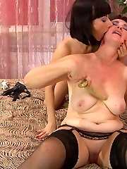 Dark-haired mommy and a woman go for lez 69ing with hot kisses and dildo play