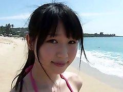 Slim Japanese doll Tsukasa Arai walks on a sandy beach under the sun