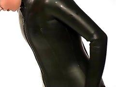 ड्रेसिंग में beavertail wetsuit और घुटने जूते पहने हुए काले लेटेक्स में