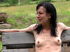 Anorexic brunette hussy gets her slender figure tied up to wooden fence outdoors