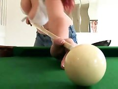Busty redhead playing pool