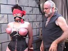 Dude clamps fully hodded and corseted bdsm brunette's cunt