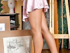 Vivacious artist stroking her seductive pantyhose dressed feet with a brush
