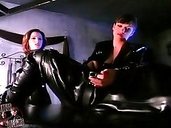 Two latex mistresses practicing bondage session on a cute submissive girl