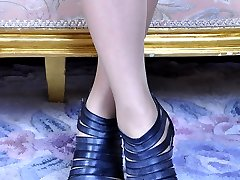 Kissable raven-head encases her perfect feet in nude hose and strappy shoes