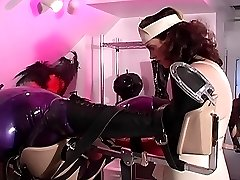 Medical domme gets her latex slave restrained connected to a dropper and examines his genitals