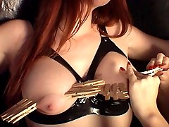 Redhead latex slave gets her big beautiful boobs clamped with multiple wooden clothespins