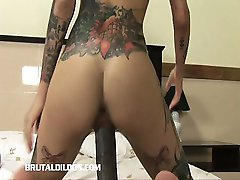 Tattoo'd babe filling her wet pussy with a brutal dildo
