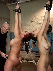 Kelly Divine and Audrey Rose are both delightfully submissive and share the tasks of enduring punishment and pleasing their master.  He tells them to undress, kiss, spank each other and lick ass.  Then, with their asses connected by a double ended dildo, he uses a massive flogger to motivate his pain sluts and makes them suck cock.  Next up is a very tricky predicament bondage position that has one girl's hair connected to the others ass hook.  A strong orgasm from one girl causes causes the other to suffer!  Lastly, they are tied in tight bondage and immobilizing positions while getting anally fucked!