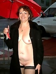 Mature UK woman naked in the steets in a rainy day