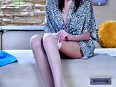 Lovely girl encases her mile-long legs in glamorous white gartered nylons