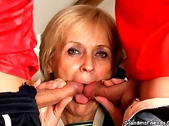 The sensual and sexy granny gets fucked by two young guys and they cum on her pretty face