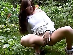Young tiny tit girl masturbates in wood.